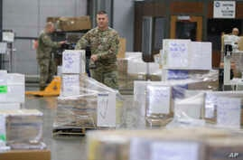 A Indiana National Guardsman lines up a pallets of medical supplies, Thursday, March 26, 2020, in Indianapolis. The medical…