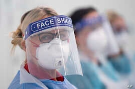 In this Thursday, April 16, 2020 photo, medical staff receive training on how to put on and remove PPE, personal protective…