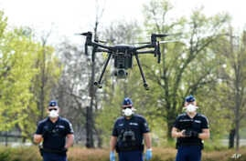 Police officers prepare a drone to find residents who fail to comply with the stay-at-home order implemented due to the…