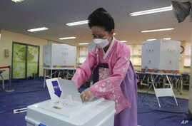 A woman wearing a face mask to help protect against the spread of the new coronavirus casts a vote for the parliamentary…