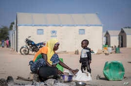 In this photo taken on Tuesday Dec. 10, 2019 a displaced Burkinabe woman and child prepare food, in the Pissila town camp, near…