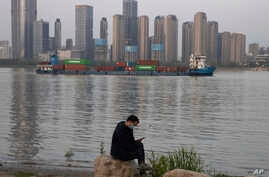 In this Monday, April 13, 2020, photo, a man wearing a mask against the new coronavirus checks his phone as a container ship…