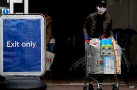 Shoppers wear face masks to protect against the coronavirus outbreak as they do their weekend shopping at a supermarket in…