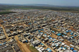 This April 19, 2020 photo shows a large refugee camp on the Syrian side of the border with Turkey, near the town of Atma, in…