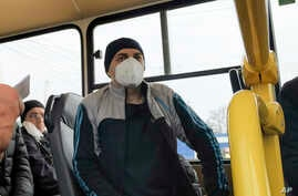 Separatist war prisoners, some of them wearing face masks to protect against coronavirus, sit in a bus after they were…