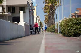 People walk along the promenade in the seaside town of Ostia, near Rome, Monday, April 13, 2020. Authorities had announced…