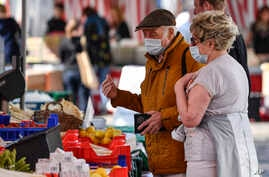 Elderly people with a face mask to protect from the coronavirus go shopping at a market in Aachen, Germany, Thursday, April 9,…
