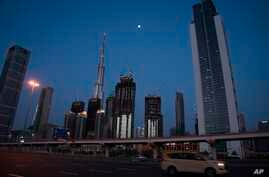 A lone taxi cab rushes down the largely empty 12-lane Sheikh Zayed Road in front of the Burj Khalifa, the world's tallest…
