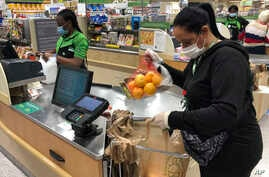 Yelitza Esteva, right, bags groceries for an order Wednesday, April 15, 2020, in Surfside, Fla. Esteva was a hairstylist. She…