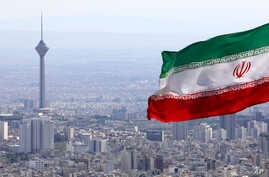 Iran's national flag waves as Milad telecommunications tower and buildings are seen in Tehran, Iran, Tuesday, March 31, 2020…
