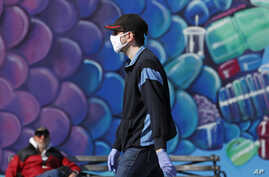 A pedestrian wears a face mask as he walks past a mural of a fish while strolling on the boardwalk at Coney Island, Thursday,…