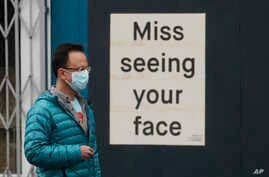A man wears a mask while walking past a sign posted on a business in San Francisco, Saturday, April 11, 2020. (AP Photo/Jeff…