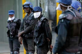 Riot police wear face masks on the streets of Harare, Zimbabwe, Tuesday, March 31, 2020. Zimbabwe went into a lockdown for 21…
