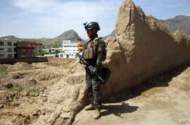 An Afghan commando stands guard at the site of a suicide bomb attack on the outskirts of Kabul, Afghanistan, Wednesday, April…
