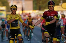 Colombia's Egan Bernal wearing the overall leader's yellow jersey, left, holds hands with Britain's Geraint Thomas after…