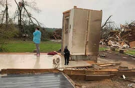 Amber Phillips stands outside the family's safe room, located on their property in Moss, Miss., following a tornado, Monday,…