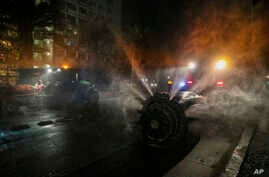 Workers use sprayers pulled by tractors to disinfect the city streets as a precautionary measure against COVID-19 in Santiago,…