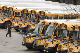 A worker passes public school buses parked at a depot in Manchester, N.H., Monday, April 27, 2020. New Hampshire public school…