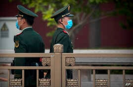 Chinese paramilitary police wearing face masks to prevent the spread of the new coronavirus stand guard along a street near…