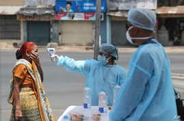 An Indian health worker checks the temperature of a woman during lockdown to prevent the spread of new coronavirus in Ahmedabad…