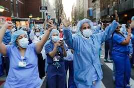 Nurses and medical workers react as police officers and pedestrians cheer them outside Lenox Hill Hospital Wednesday, April 15,…