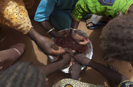 In this Tuesday, May 1, 2012 photo, Maryam Sy and five of her nine children share a meager bowl of tamarind-flavored porridge,…