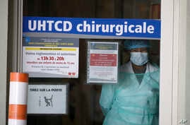 A medical staff looks through a door in an hospital Wednesday April 1, 2020 in Rennes, western France. France is evacuating 36…