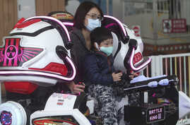 Visitors wear face masks to protect against the spread of the new coronavirus at Taipei Children's Amusement Park in Taipei,…