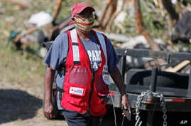 Red Cross volunteer Katherine Campbell Hudson wears her face mask as she visits tornado damaged residences in this south…