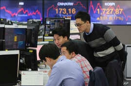 Currency trader watch monitors at the foreign exchange dealing room of the KEB Hana Bank headquarters in Seoul, South Korea,…