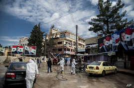 FILE - In this March 24, 2020 file photo, workers spray disinfectant to prevent the spread of the coronavirus, on a street…