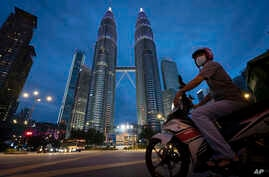Food delivery rider waits at a traffic junction in front of Twin Towers to deliver food during the movement control order due…