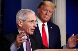 FILE - In this April 22, 2020 file photo President Donald Trump watches as Dr. Anthony Fauci, director of the National…