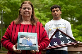 In this Friday, May 22, 2020, photo Florence Hopp, left, holds a photograph of herself and her husband Robert Hopp during a…