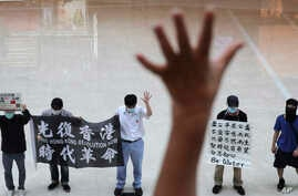 "Protesters gesture with five fingers, signifying the ""Five demands - not one less"" in a shopping mall during a protest against…"