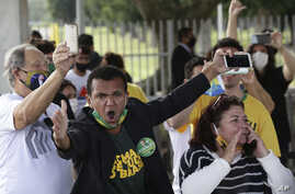 Supporters of Brazil's President Jair Bolsonaro, wearing face masks amid the new coronavirus pandemic, yell out against…