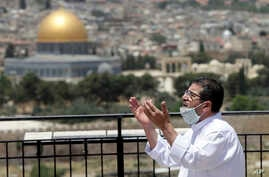 A muslim man prays in east Jerusalem's Mount of Olives, overlooking the Dome of the Rock and al-Aqsa mosque compound, which…