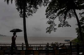 An Indian man walks with his umbrella in the middle of heavy wind and rain along the river Brahmaputra in Gauhati, India,…