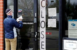 FILE - In this April 30, 2020 file photo, a man writes information in front of Illinois Department of Employment Security in…