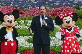 Joe Schott, center, president and general manager of Shanghai Disney Resort, speaks, along with Mickey and Minnie Mouse, during…