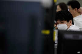 A currency trader wearing a face mask watches computer monitors at the foreign exchange dealing room in Seoul, South Korea,…