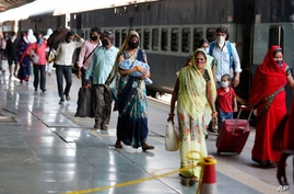 Migrant laborers from Gujarat state walk at a railway station after arriving in their home state in Prayagraj, India, Wednesday…