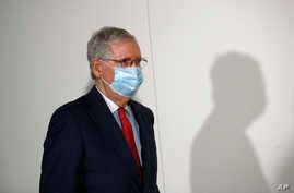 Senate Majority Leader Mitch McConnell of Ky., wears a face mask used to protect against the spread of the new coronavirus as…