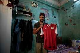 In this May 9, 2020 photo, 28-year-old defender Mahrous Mahmoud holds up his Egyptian national football team jersey he trains…