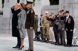 World War II veterans salute as Taps is played during a ceremony at the World War II Memorial to commemorate the 75th…