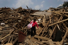 A woman carries her salvaged goods through the rubble of destroyed houses following a massive earthquake in the town of…