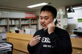 In this May 11, 2020 photo, Lee Jong-geol, general director of the gay rights advocacy group Chingusai talks on the phone…