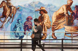 Travelers wear face masks as they pass by a mural in the main terminal of Denver International Airport as easing of…