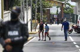 Security forces, back, leave a facility in the Macuto area in La Guiara, Venezuela, Sunday, May 3, 2020. Interior Nestor…