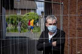 Julian, Romanian worker who stands behind the fence that was set up at the entrance of a housing of Romania slaughterhouse…